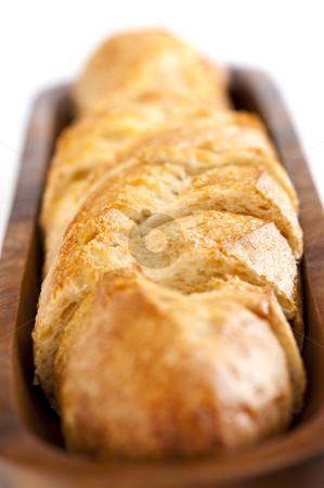 Baguette stock photo, Isolated sliced baguette bread in wooden dish by Elena Elisseeva