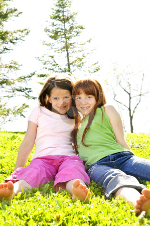 Young sisters stock photo, Portrait of happy girls sitting on grass by Elena Elisseeva