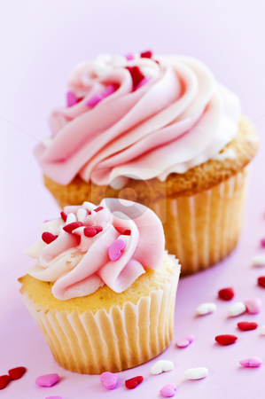 Cupcakes stock photo, Big and small cupcakes with icing and sprinkles by Elena Elisseeva
