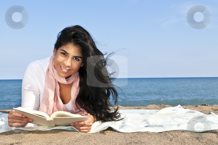 Young native american woman reading stock photo, Portrait of beautiful smiling native american girl reading book at beach by Elena Elisseeva