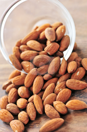 Almonds stock photo, Raw almonds spilling out of small glass bowl by Elena Elisseeva