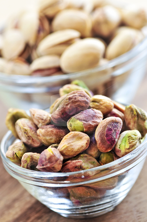 Pistachio nuts in glass bowls stock photo, Close up of pistachio nuts in glass bowls by Elena Elisseeva