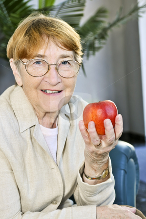 Elderly woman with apple stock photo, Elderly woman with glasses holding apple and smiling by Elena Elisseeva