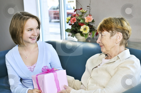 Granddaughter visiting grandmother stock photo, Granddaughter giving a present to her grandmother by Elena Elisseeva