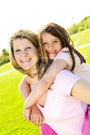 Mother and daughter piggyback stock photo, Portrait of happy mother giving piggyback ride to child by Elena Elisseeva