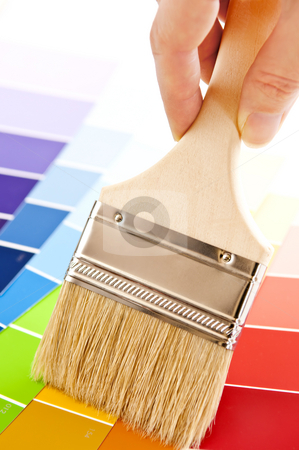 Hand holding paintbrush stock photo, Hand holding paintbrush over color card samples by Elena Elisseeva