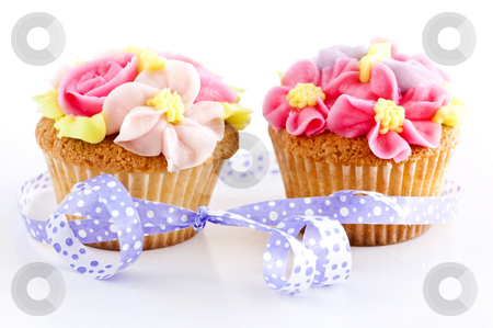 Cupcakes stock photo, Pair of cupcakes with icing flowers and ribbon by Elena Elisseeva