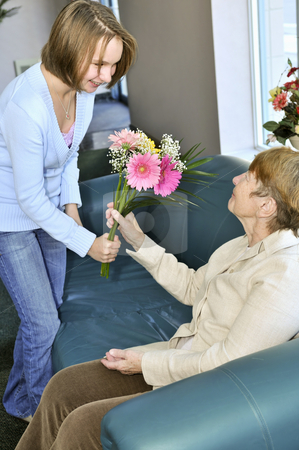Granddaughter visiting grandmother stock photo, Granddaughter bringing colorful flowers to her grandmother by Elena Elisseeva