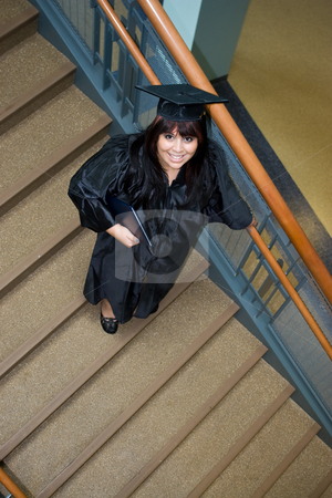 Graduation Time stock photo, A recent graduate poses on a stairway with her diploma in hand. by Todd Arena