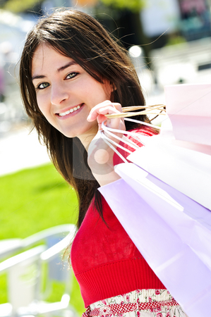 Young woman shopping stock photo, Portrait of young woman with shopping bags at outdoor mall by Elena Elisseeva