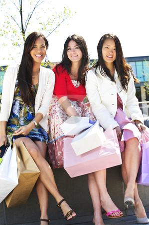 Young girlfriends shopping stock photo, Three young girl friends holding shopping bags at mall by Elena Elisseeva