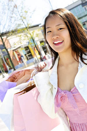 Asian woman shopping stock photo, Young korean woman with shopping bags at outdoor mall by Elena Elisseeva