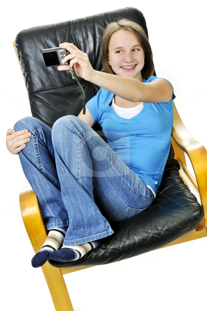 Girl taking self portrait stock photo, Young girl taking picture of herself in leather chair by Elena Elisseeva