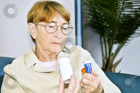 Elderly woman reading pill bottles stock photo, Elderly woman reading warning labels on pill bottles with medication by Elena Elisseeva