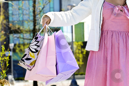 Woman holding shopping bags stock photo, Young girl holding shopping bags at mall by Elena Elisseeva