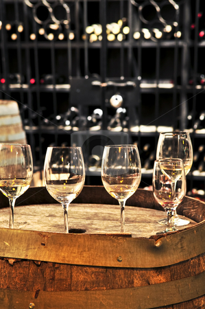 Wine  glasses and barrels stock photo, Row of wine glasses on barrel in winery cellar by Elena Elisseeva