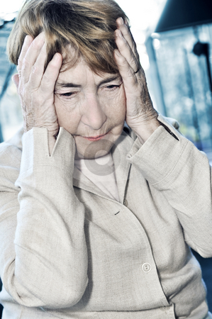 Elderly woman holding head stock photo, Senior woman holding head in her hands by Elena Elisseeva