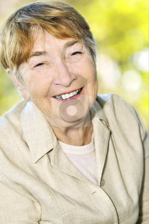 Elderly woman smiling stock photo, Senior woman laughing and smiling with abstract background by Elena Elisseeva