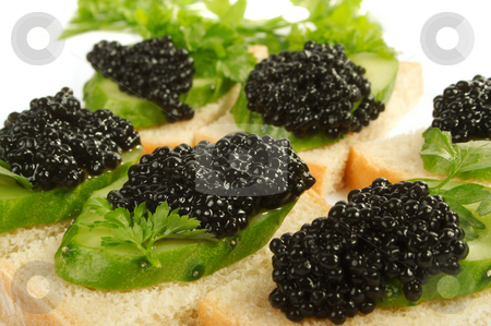 Caviar black stock photo, Sandwiches with black caviar and a cucumber on a white background. by Sergey Goruppa