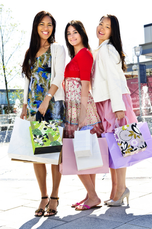 Group of young girlfriends shopping stock photo, Group of young girl friends holding shopping bags at mall by Elena Elisseeva