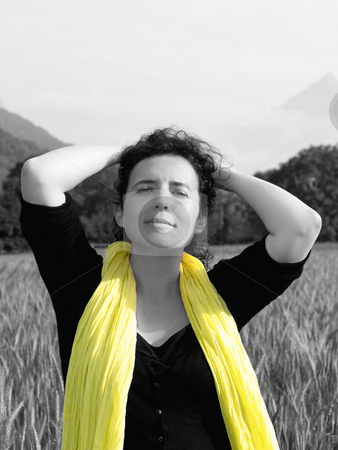 Woman in barley field stock photo, Photo of an attractive french woman wearing a yellow scarf standing in a barley field with mountains in the background by Laurent Dambies