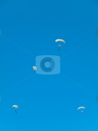 Group of parachutists stock photo, Group of white parachute jumpers  against pure blue sky by Laurent Dambies
