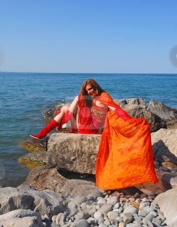 The fire girl. stock photo, The woman, representing fire, dressed in red, sitting on the shore of lake Ontario in bright sunshine and the waves coming to shore. by Horst Petzold