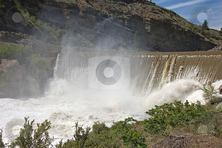 Enslow Dam Washington stock photo, Photo of Enlow Dam in Washington state with desert type mountain, the muddy river going over the fall and mist rising up. by Valerie Garner