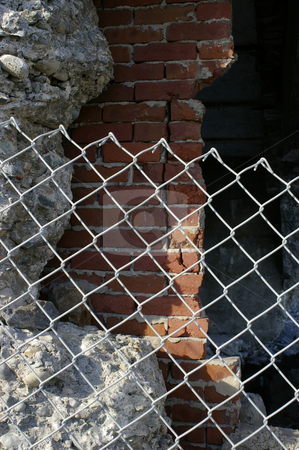 Crumbling walls stock photo, Crumbling concrete and brick walls behind a chain link fence. by Tom Weatherhead