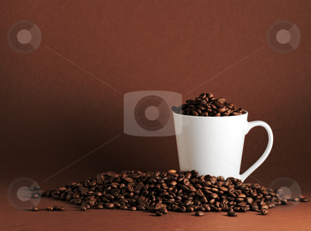 Coffee beans and mug landscape stock photo, White mug surrounded by coffee beans on coffee colored background with plenty of copy space by Paul Turner