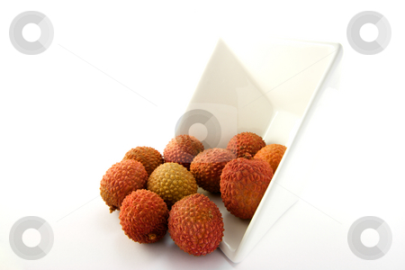 Lychee Spilling out of a Dish stock photo, Lychee spilling out a dish with clipping on a white background by Keith Wilson