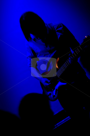 Rock guitarist stock photo, Silhouette of a Rock guitarist on stage, cast in the blue light of a directional spot by Corepics VOF