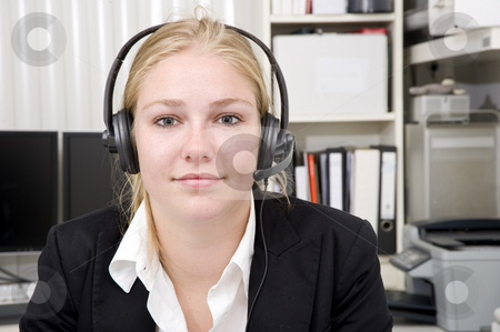 Receptionist stock photo, A woman wearing a head set with microphone as receptionist for a small business. An office setting in the background by Corepics VOF