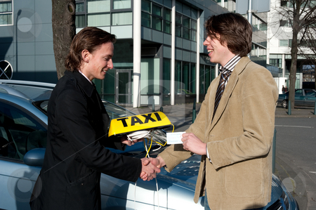 Getting the taxi license stock photo, A government official handing a taxi license and sign to a newly appointed taxi driver whilst shaking his hand by Corepics VOF