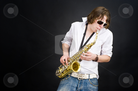 Saxophone player stock photo, A musician in a white shirt jamming away on a saxophone, improvising by Corepics VOF