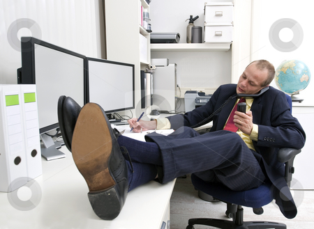 On the phone stock photo, Businessman with his shoes on the desk, talking on the phone whilst making notes and holding another call by Corepics VOF