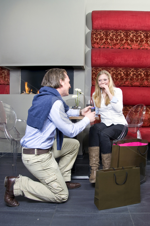 Proposing stock photo, A man proposing to a woman in front of a restaurant fireplace by Corepics VOF