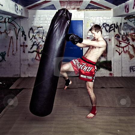 Knee punch stock photo, Athletic muay thai boxer giving a forceful knee kick during a training with a boxing bag by Corepics VOF