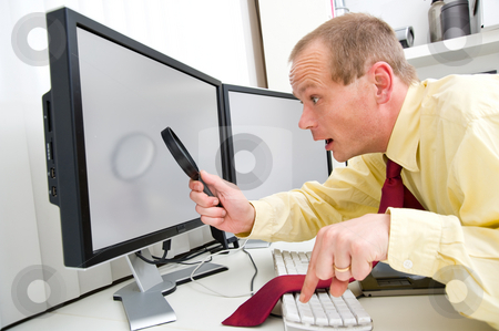 Computer stock photo, A man being surprized while scruitining  a computer monitor with a magnifying glass, his left index finger hovering above the Escape key by Corepics VOF