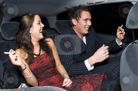 Backseat fun stock photo, A young couple laughing in the backseat of a car after a night out, smoking cigarettes by Corepics VOF