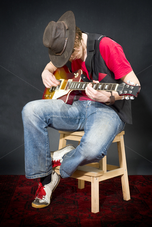 Sitting Guitar player stock photo, A musician wearing an old, leather hat, playing on his guitar whilst sitting on a stool by Corepics VOF