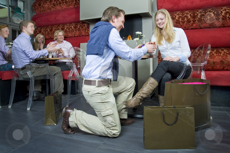 Succesful proposal stock photo, A youngwoman accepting her boyfriends proposal, whilst the other guests at a restarant applaud the young couple by Corepics VOF
