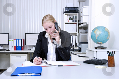 Office work stock photo, A businesswoman on the phone and taking notes in an office environment by Corepics VOF