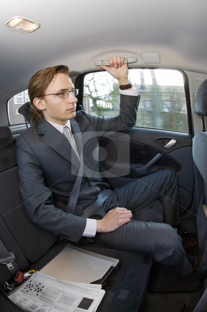 Businessman in a taxi stock photo, A businessman riding in the backseat of a taxi with laptop and newspaper next to him by Corepics VOF