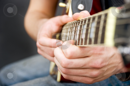 Guitar hands stock photo, The hands of a sitting guitarist on the fingerboard. Selective focus on the musicians left hand by Corepics VOF