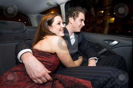 Young lovers in the backseat stock photo, A couple of young lovers in the backseat of a car at night by Corepics VOF