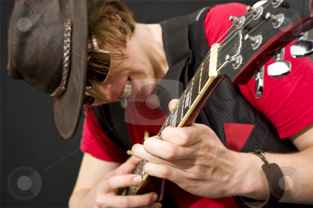 Guitar Solo stock photo, A trendy looking guitar player during a heavy guitar solo. Selective focus on the musicians left hand by Corepics VOF