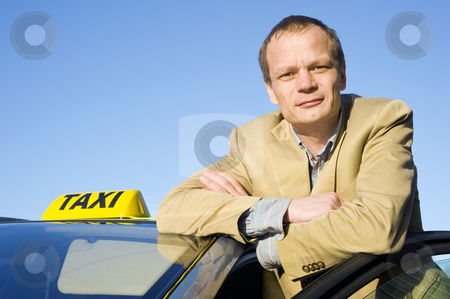 Taxi driver stock photo, A taxi driver posing behind the front door of his cab by Corepics VOF