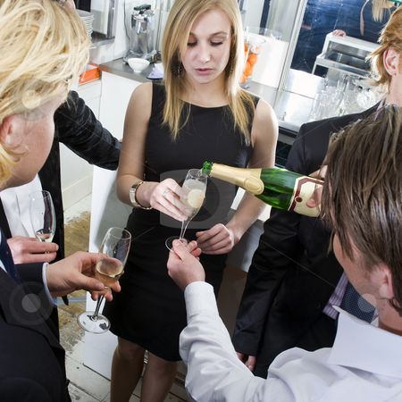 Refill stock photo, Waiter, refilling champagne glasses from the bottle in a bar on New years eve by Corepics VOF