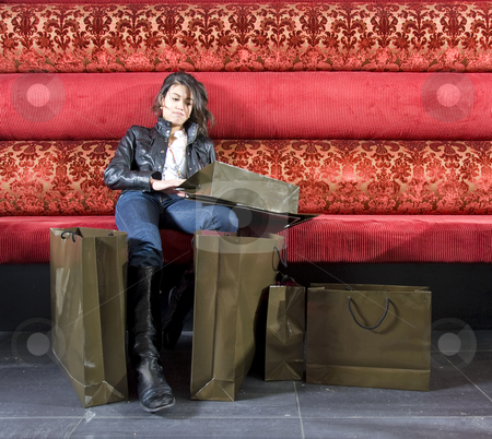 Exhausted shopper stock photo, An asian woman, exhausted from shopping, on a pillowed bench by Corepics VOF